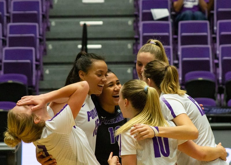 The volleyball team laughs in the huddle after scoring a point.