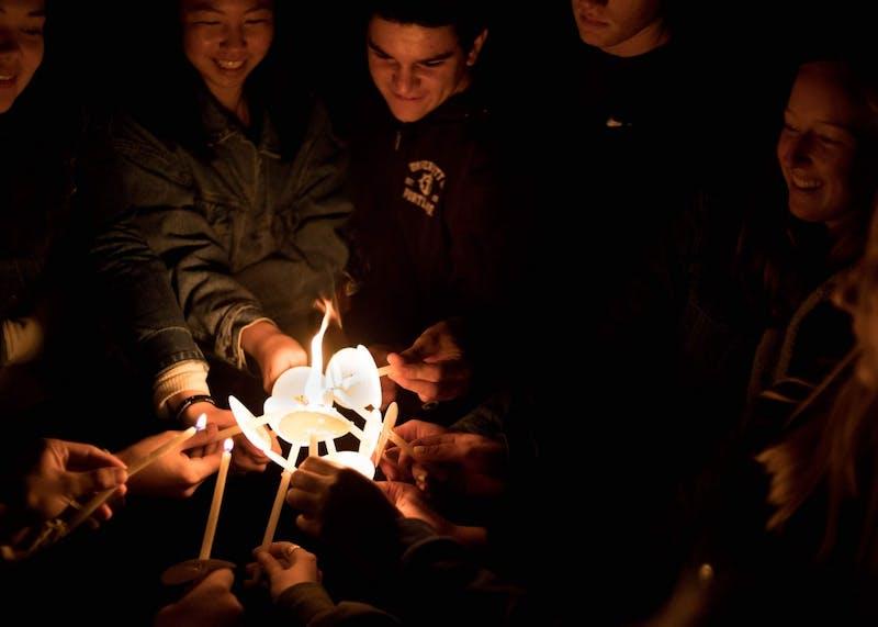 Members of Owen Klinger's workshop group unite their candles.