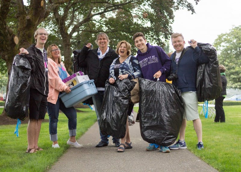 Freshmen Dawson Kay (far left) and Kent Scollard (second from right) and their parents express their excitement for unpacking during University of Portland's 2018 move-in day.