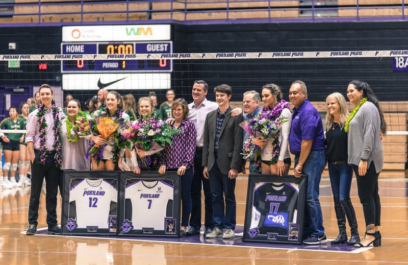 Graduating players Katie Barker, Emma Scanlan and Shayla Hoeft pose with their coaches and families for Senior Night.