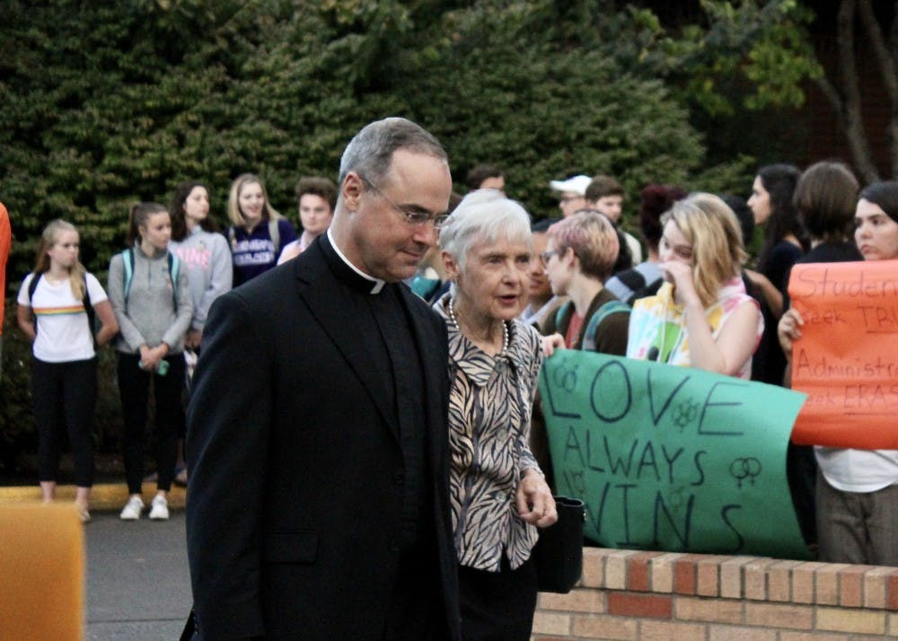 Fr. Paul Scalia passes through the protest with his mother, Maureen Scalia, widow of Supreme Court Justice Antonin Scalia. ASUP organized the demonstration to protest Scalia's involvement in an anti-LGBTQ group and statements he has made about homosexuality.