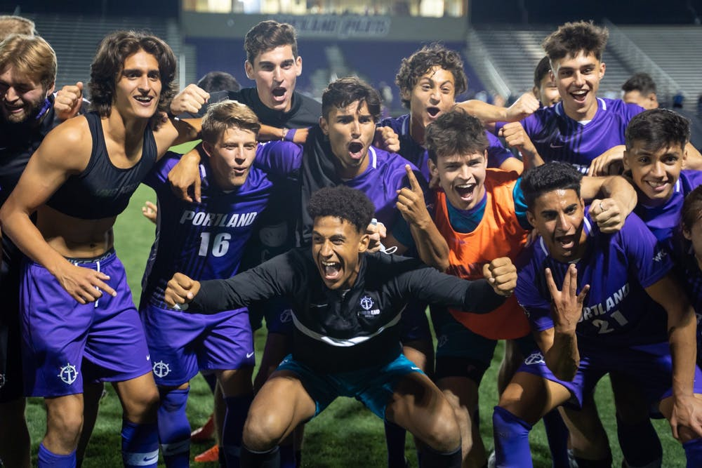 The men's team celebrates with their fans in front of the student section after the game. The final score was 2-0 for the Pilots.