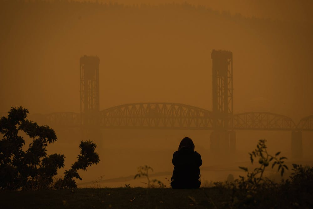 """A lone figure stares out at the Burlington Railroad Bridge from The Bluff. Air in Portland will continue to be """"very unhealthy"""" in the coming days."""