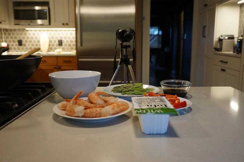 A camera records how to create cheap, basic, and versatile foods. Pilots After Dark is demonstrating how to do this with a new webinar series, Cooking it UP. Photo Illustration By Marek Corsello.