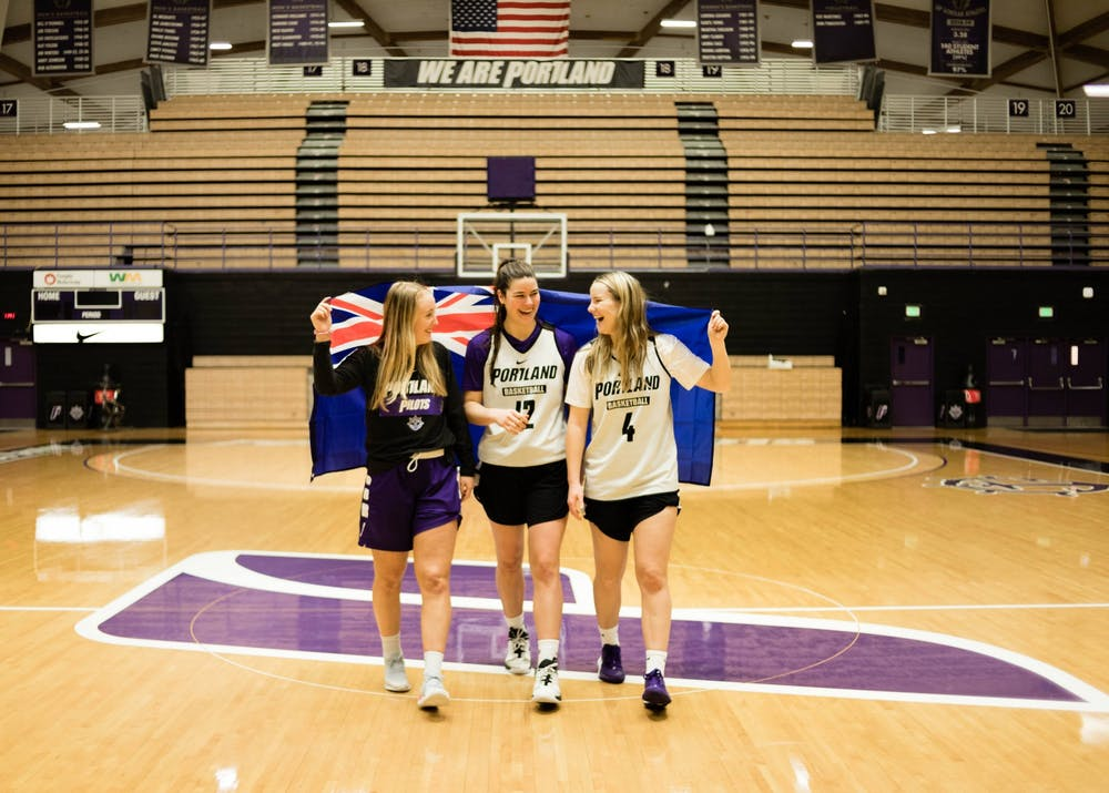 (From left to write) Haylee Andrews, Alex Fowler, and Keeley Frawley walk down the court with the Australian flag wrapped around them.