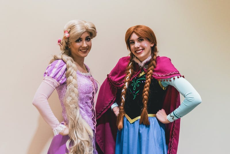 Two princesses pose after attending a hospital visit. They're a part of UP's chapter of A Moment of Magic, a non-profit where college students dress as children's favorite characters and visit them in the hospital.
