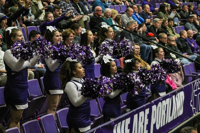 The Cheer Club cheers on the men's basketball team from the stands.