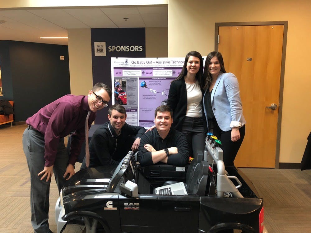 Team members Jacob Wolwowicz, Parker Elliot, Ally Fox, Philipp Holzmann and Laura Pickering pose in front of a Dodge Ram Power Wheel Car, which was provided to them by Go Baby Go. Photo courtesy of Pickering.
