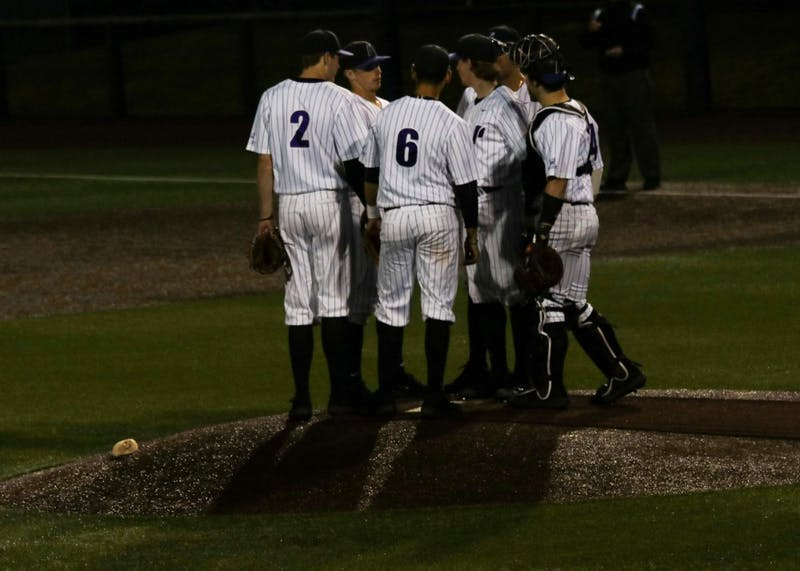 The team comes together to strategize after LMU scores a run.