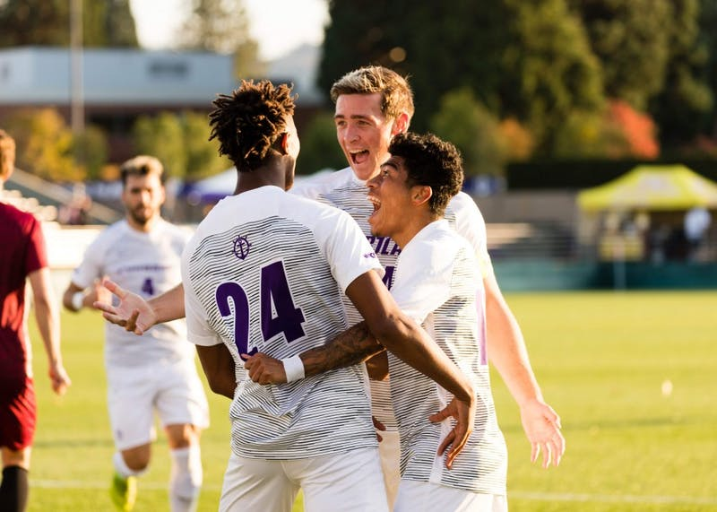 Freshman defender Delentz Pierre celebrates his second collegiate goal with teammates Brian O'Hara and Rey Ortiz.