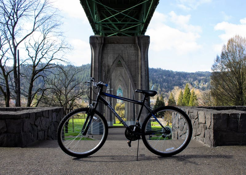 A bike sits below St. Johns Bridge at the entrance to Cathedral Park. Biking is a great way to get across town while staying active.