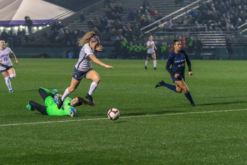 Senior forward Kimberly Hazlett leaps over the keeper and heads towards the goal.