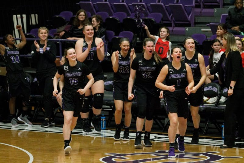 An ecstatic Portland bench rushes the court after the final whistle to congratulate their teammates on their last victory of the season.