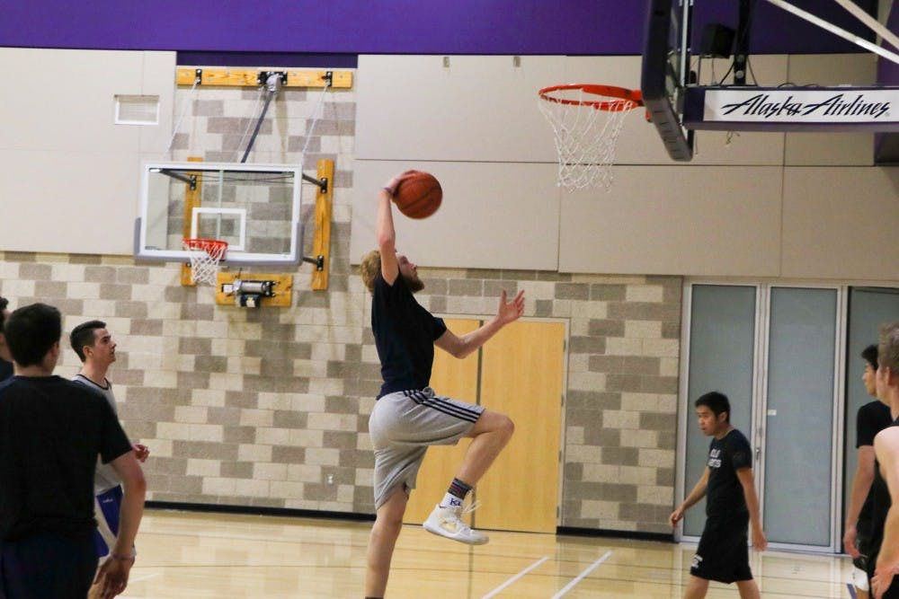 Freshmen Dylan de Jong goes up for a dunk at club basketball practice.