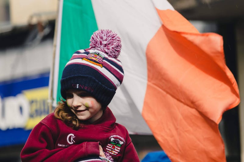 A young girl smiles at the parade spectators while her camogie team walks through Galway city center in 2019. Submission courtesy of Molly Lowney.