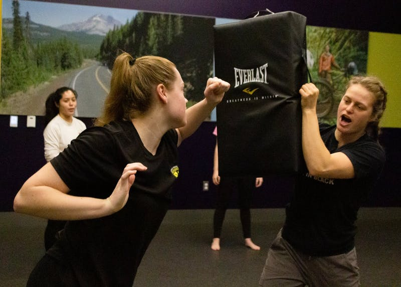 Instructor Anika Sproull holds a punching bag for students to practice a palm heel strike.