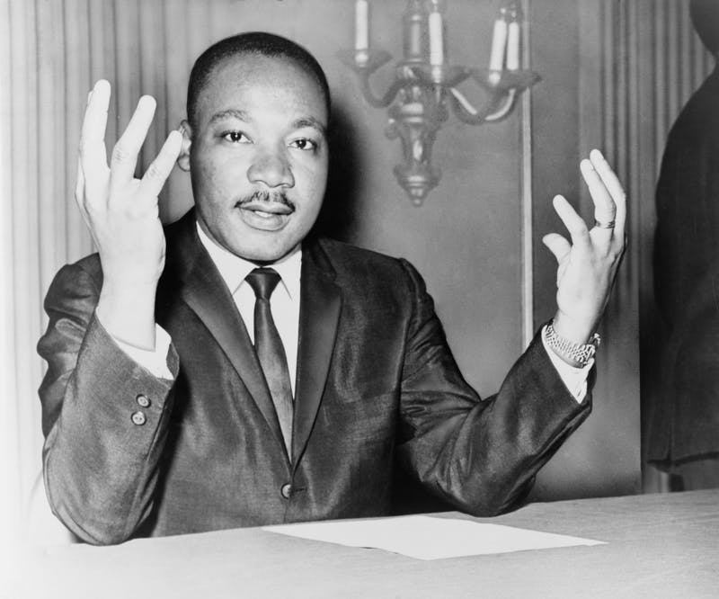 Rev. Martin Luther King, head-and-shoulders portrait, seated, facing front, hands extended upward, during a press conference / World Telegram & Sun photo by Dick DeMarsico. Photo: Wikimedia Commons