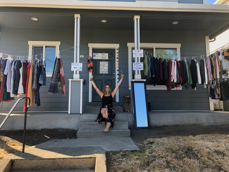 Maddie Olson, founder of Worn Relief, poses in front of her pop-up sale inventory.
