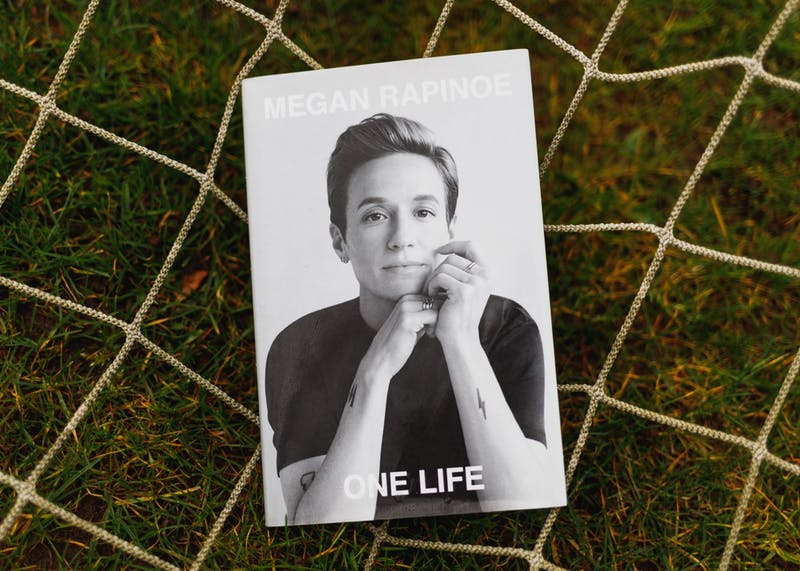 """Megan Rapinoe's """"One Life"""" was published in Nov. 2020. The book is a memoir of reflections on soccer, sexuality and social justice.Photo Illustration by Molly Lowney"""