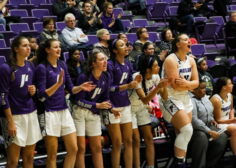 The team cheers after Josie Matz makes a three point shot to increase the lead late in the fourth quarter.