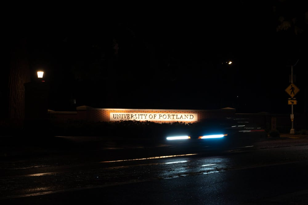 A car drives past the University of Portland entrance at night. Many UP students live in  houses and apartments outside of the campus in University Park.