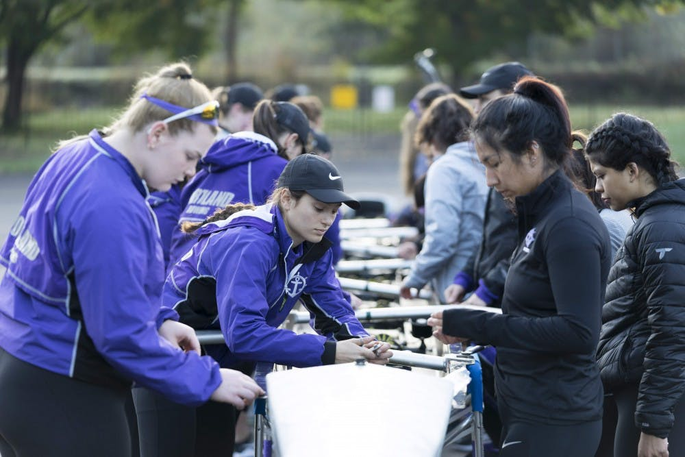 Senior captain Jacquelyn Bass helps prepare a boat before rowing practice.