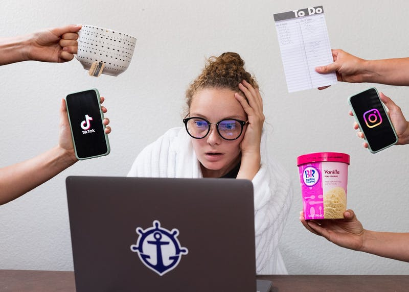 A UP student tries to focus on their online work in a distracting home environment. Photo Illustration by Molly Lowney