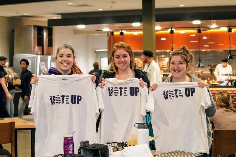 Students hold up VoteUP shirts in the Pilot House during the 2016 presidential election.