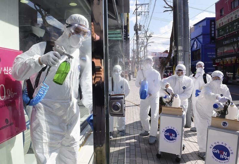 Officials in protective gear disinfect a building in Seoul amid the spread of the new coronavirus. Due to concerns about the virus, UP's E-Scholars group canceled its Spring Break trip to South Korea and is going to New Zealand instead. (Kyodo via AP Images)