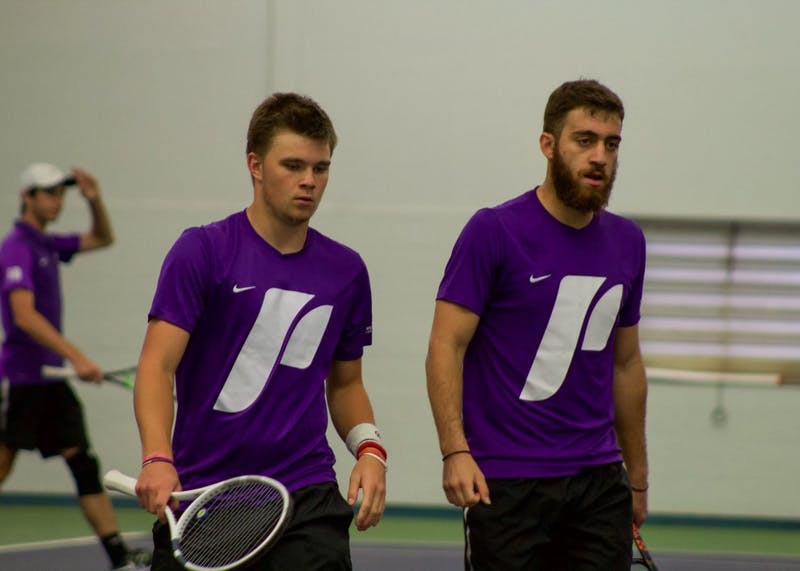 Freshmen Sema Pankin and Eleftherios Neos walk off the court after their doubles victory.