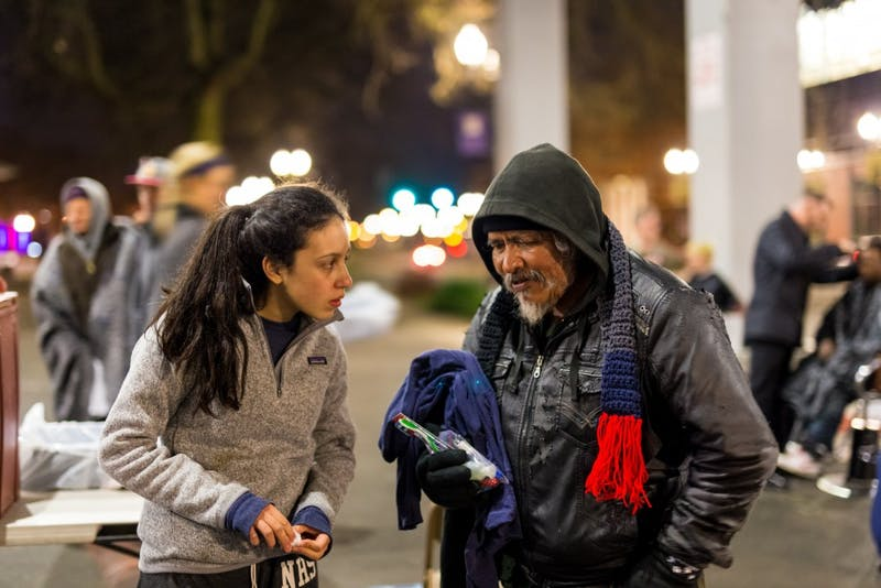 A Night Strike volunteer engages in conversation with a man taking advantage of the services under the bridge. Photo courtesy of Because People Matter.
