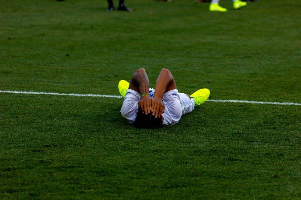 Senior midfielder Rey Ortiz lies down after the loss.