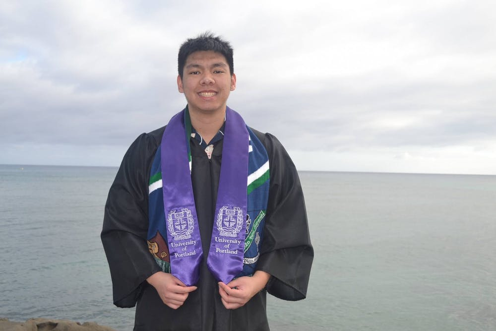 Isley Cachero poses for a picture in his graduation robes. Photo courtesy of Kiley Cachero.
