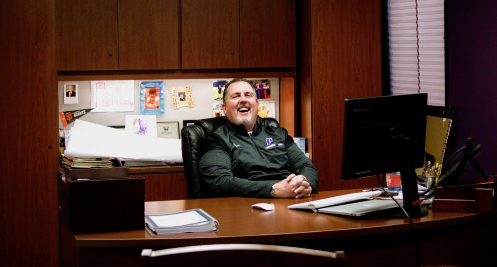 Leykam laughs at his desk in his office in the Chiles Center.