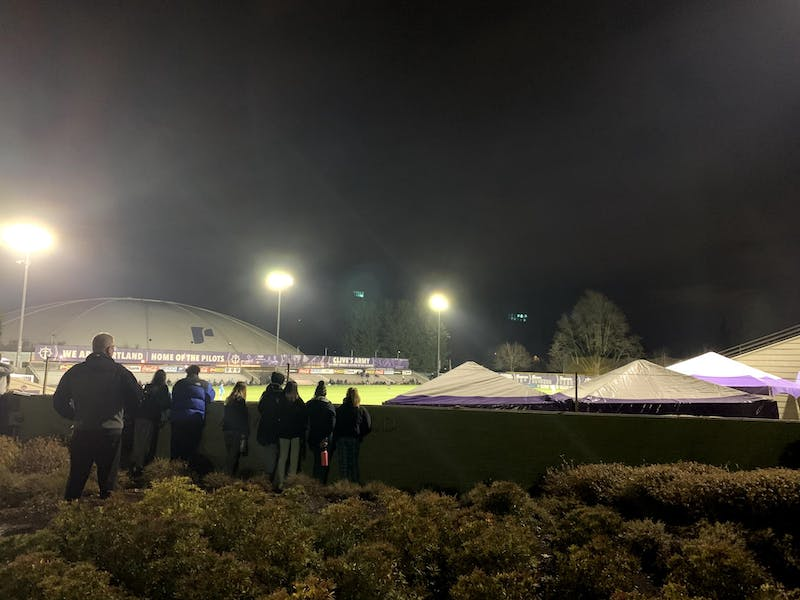 Students watch the men's soccer opener from outside the stadium. Spectators will not be allowed to watch athletic matches this season.