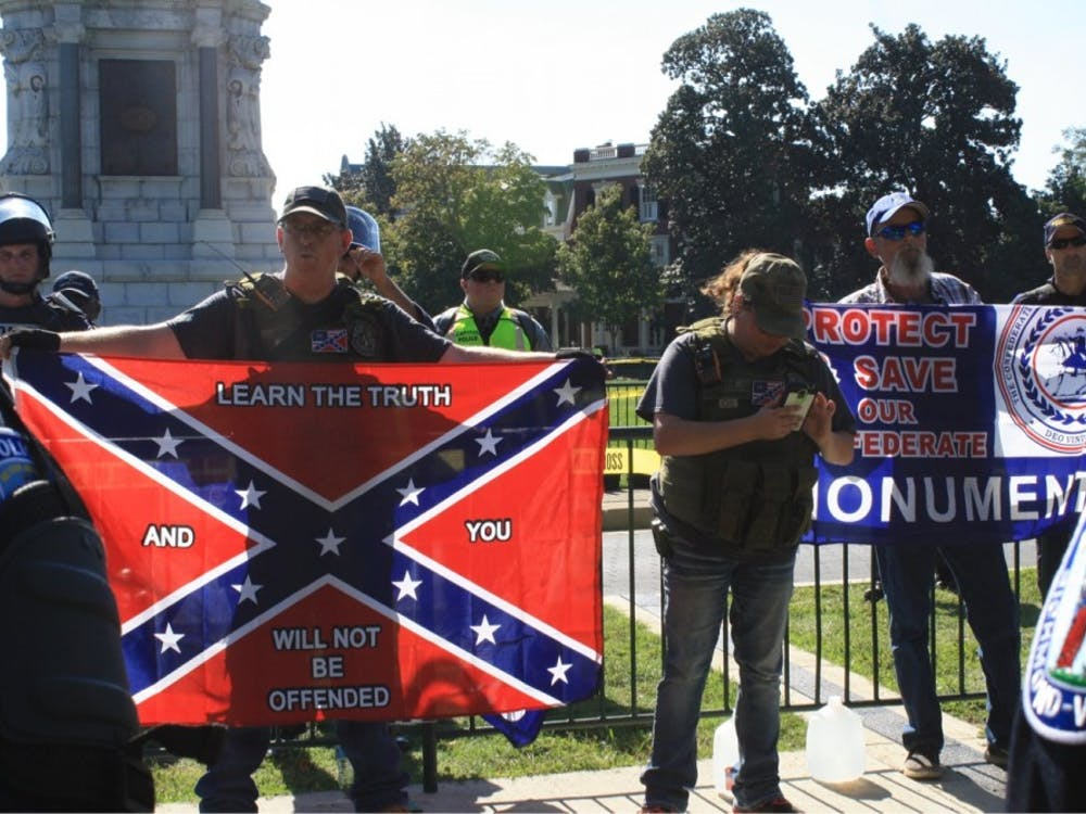 Members of a Tennessee-based Confederate group stand behind a police blockade in front of the Robert E. Lee statue.