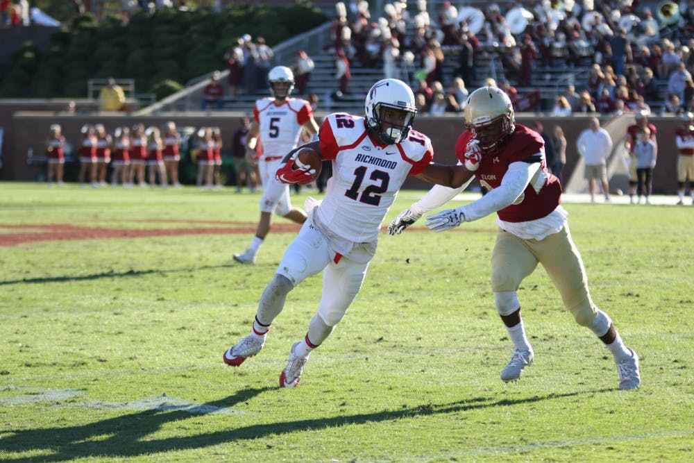<p>Senior receiver Brian Brown uses his arm&nbsp;to avoid a tackle during Richmond's win over Elon Saturday.&nbsp;</p>