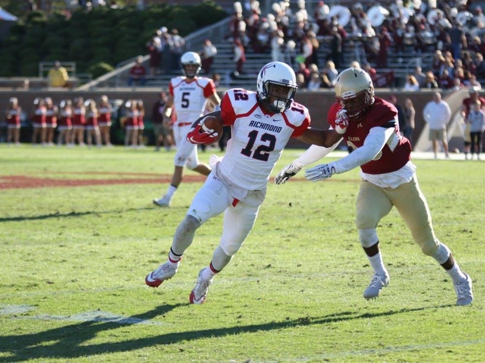 Senior receiver Brian Brown uses his arm to avoid a tackle during Richmond's win over Elon Saturday.