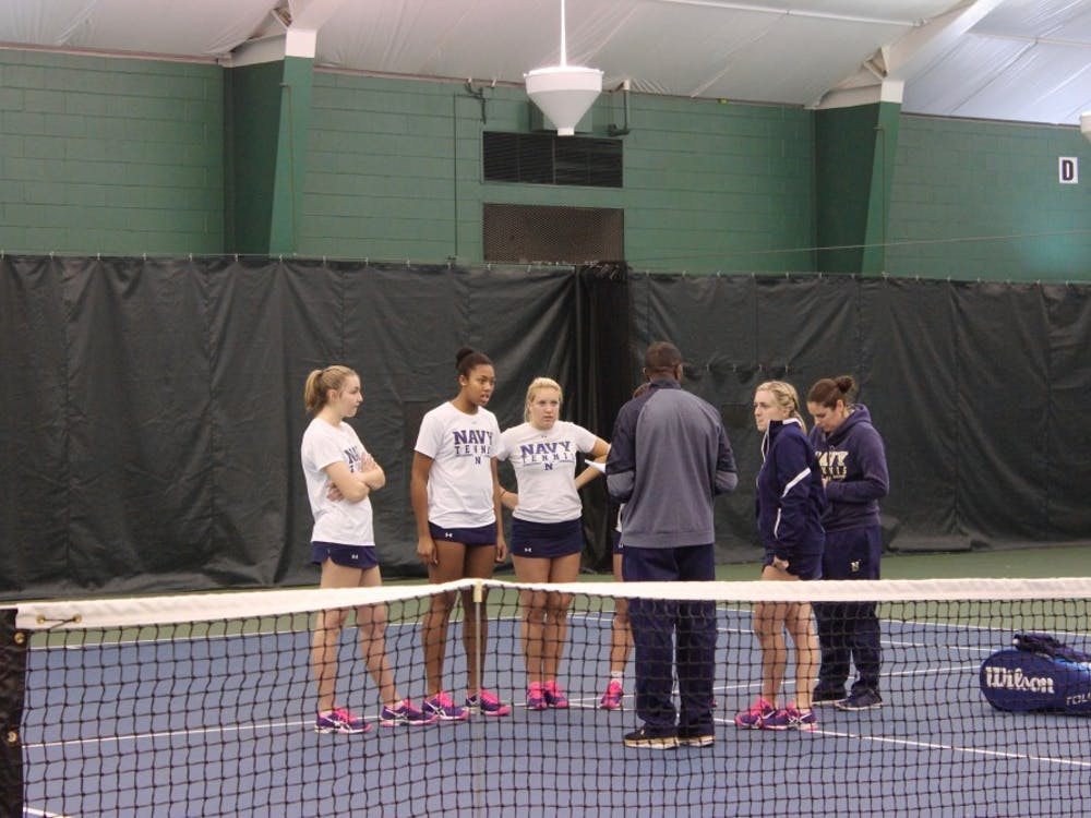 Navy coach gathers with the team to reflect on the doubles matches and talk strategy before the singles matches begin.