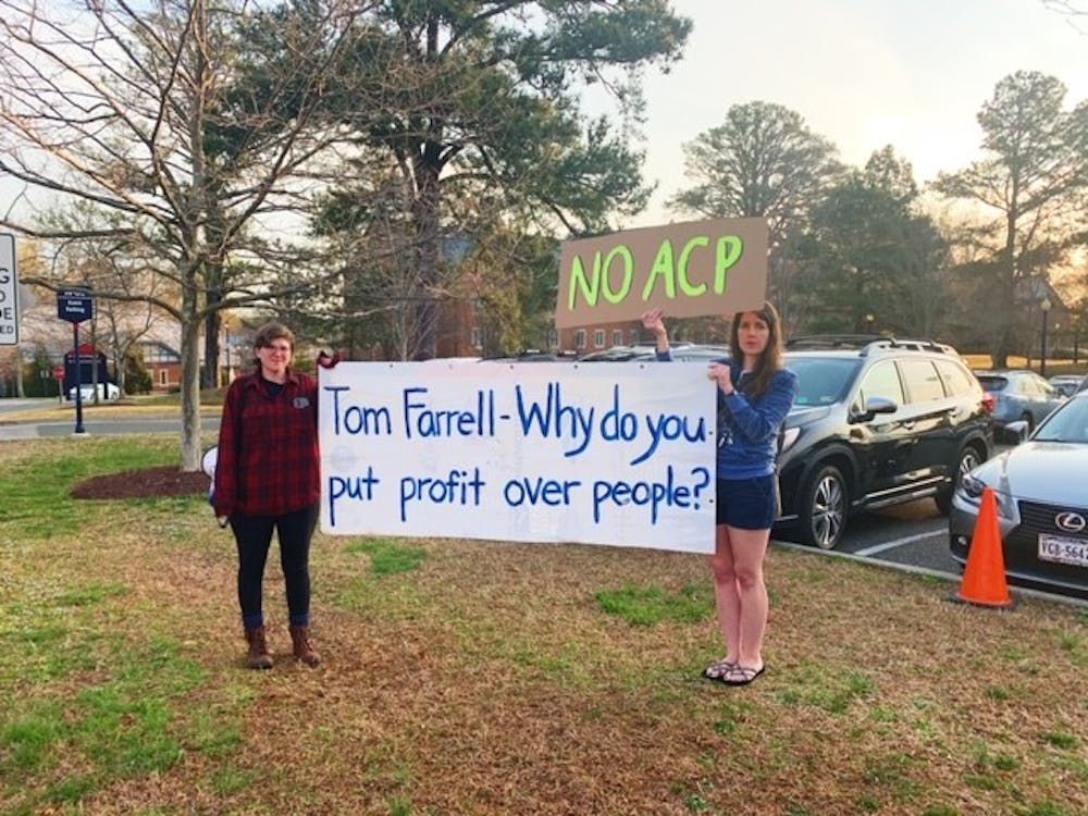 Two protesters from The Virginia Student Environmental Coalition stand outside the Jepson Alumni Center.