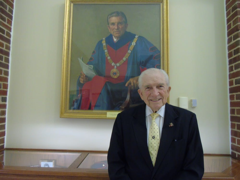 <p>E. Bruce Heilman stands in front of his portrait hanging in the Heilman Dining Center.</p>