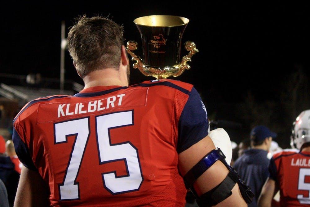 <p><em>Patrick Kliebert, redshirt senior offensive lineman, lifts the Capital Cup after winning the game.&nbsp;</em></p>