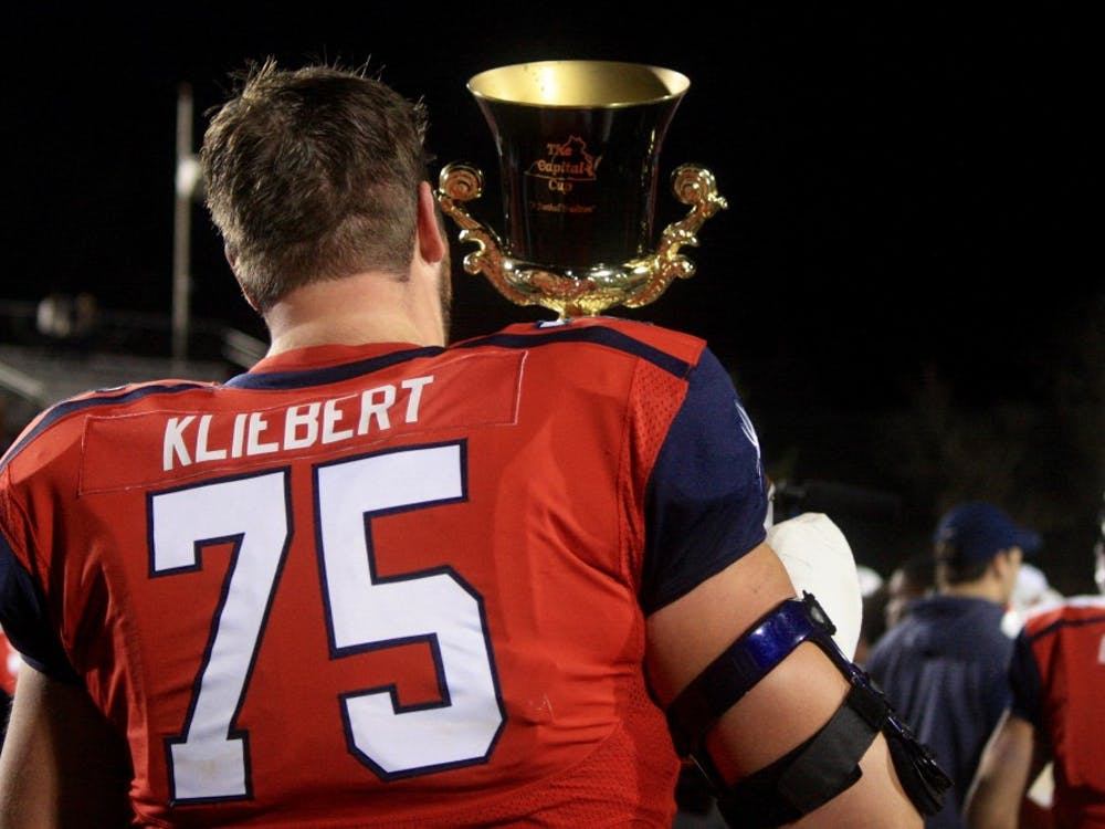 Patrick Kliebert, redshirt senior offensive lineman, lifts the Capital Cup after winning the game.