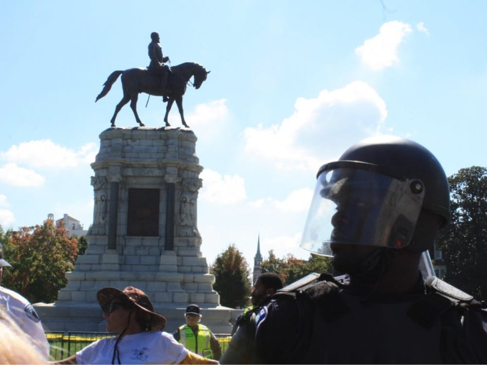 A Richmond police officer stands guard in front of the Robert E. Lee statue on Saturday during a pro-Confederate rally on Monument Ave.
