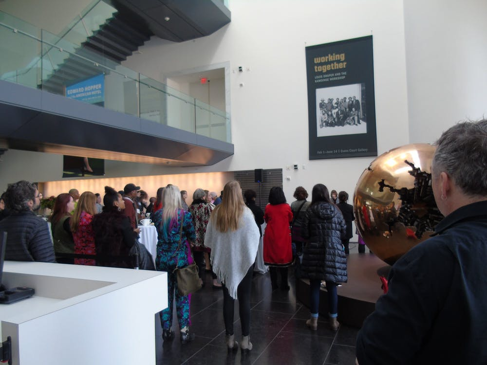 """<p>Onlookers stand at the opening of """"Working Together: Louis Draper and the Kamoinge Workshop,"""" a new exhibit at the Virginia Museum of Fine Arts. The exhibit opened on Feb. 1, 2020.</p>"""