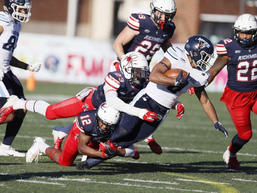 Sophomore Markus Vinson (12) and junior Daniel Jones (23) make a tackle during the Spiders' last home game of the season on Nov. 10.