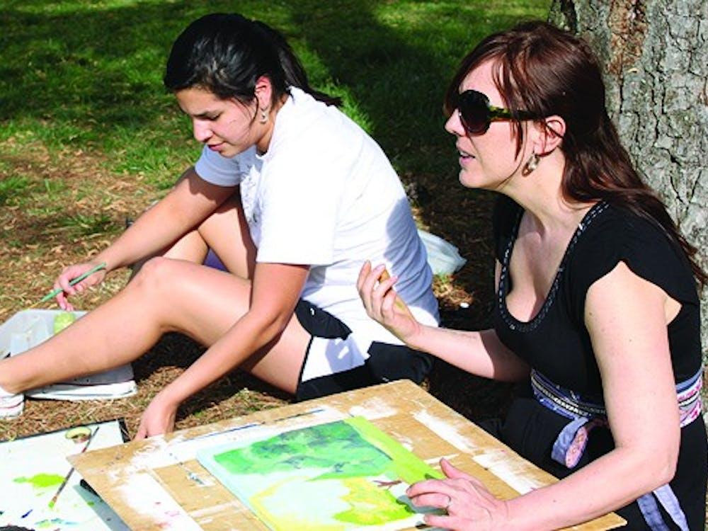 Professor Hiede gives artistic advice to sophomore, Lourdes Figueroa.