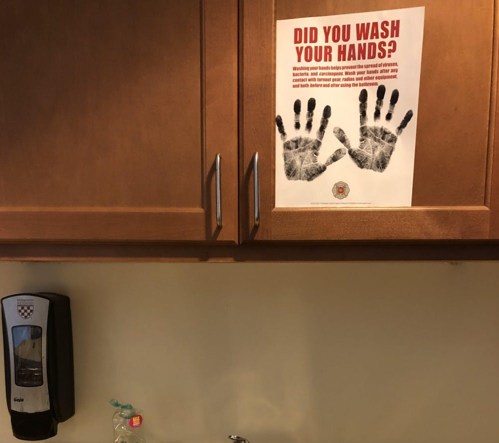 A sign reminds students to wash their hands above a sink.