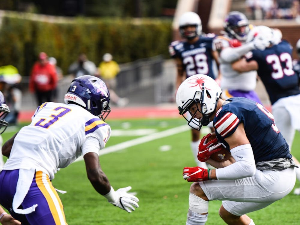 Wide receiver graduate student Charlie Fessler avoids Albany's defense during the game on Saturday, Oct. 5, 2019.
