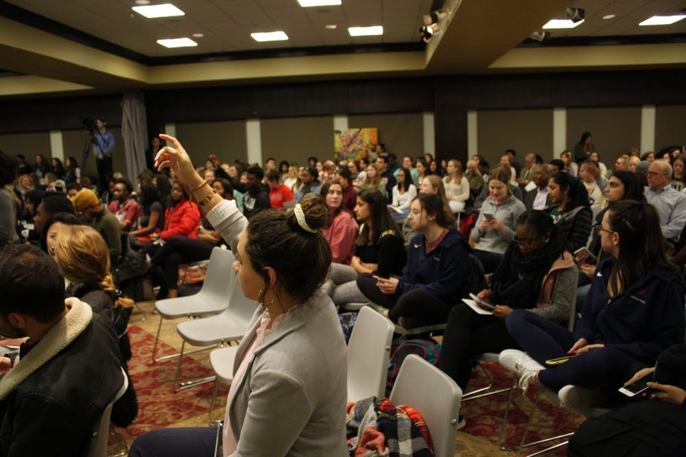<p>Students raise their hands to indicate that there are available seats near them before the start of the community meeting on Jan. 30.</p>